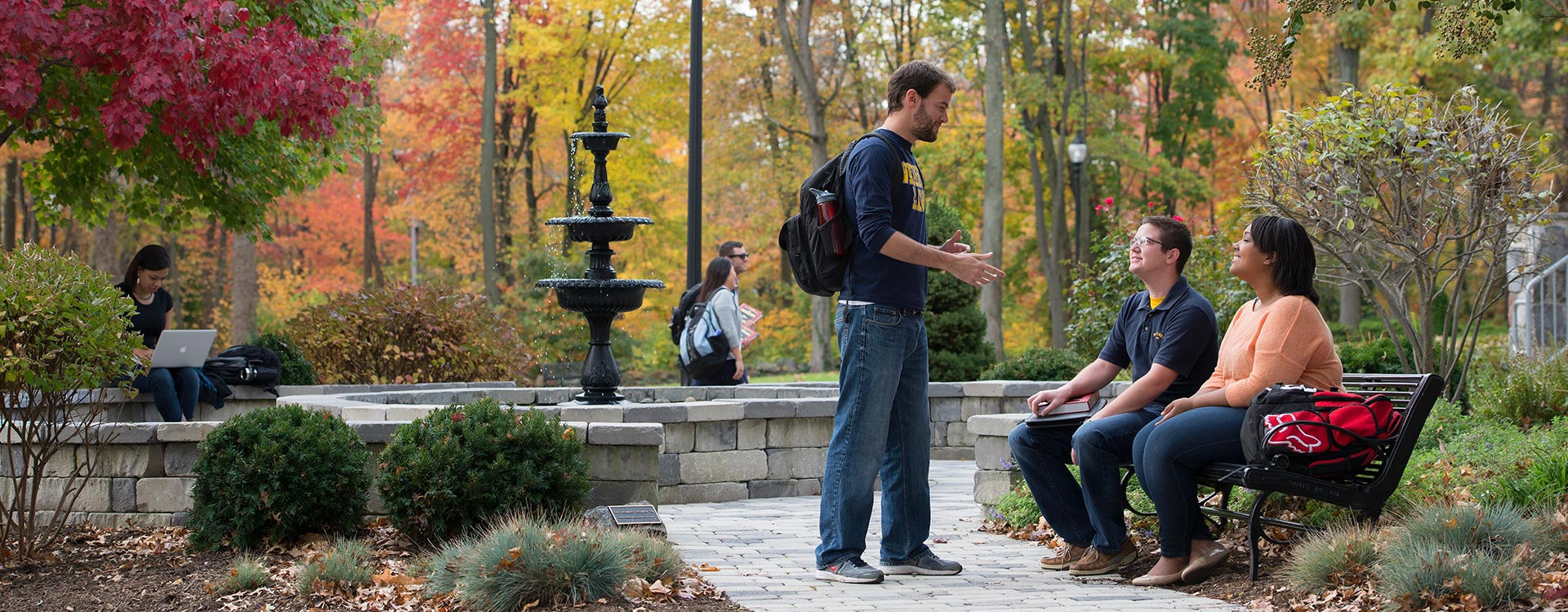 Three students conversing in a park